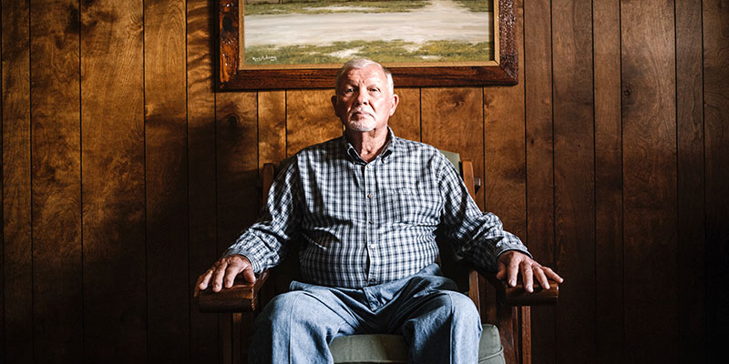 An older man sitting in his home