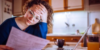 A woman looking at a financial document within the kitchen of her home
