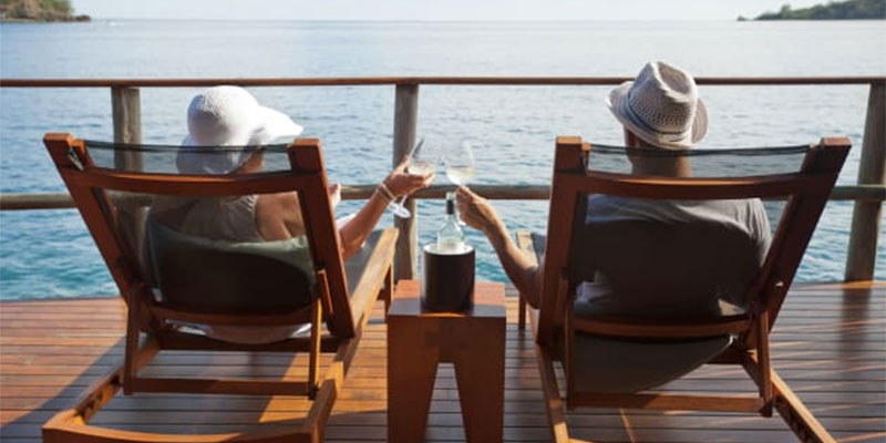 Retired couple on a deck overlooking water toasting each other with champagne