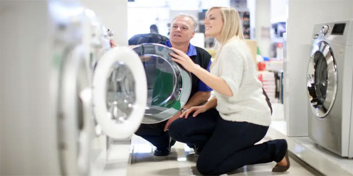 Man and a woman inspecting a brand new washing machine